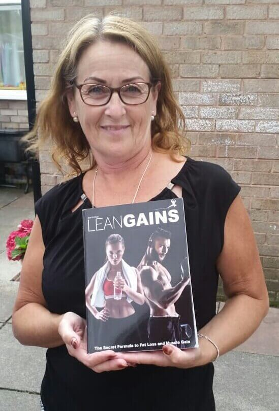 woman holding lean gains fitness book