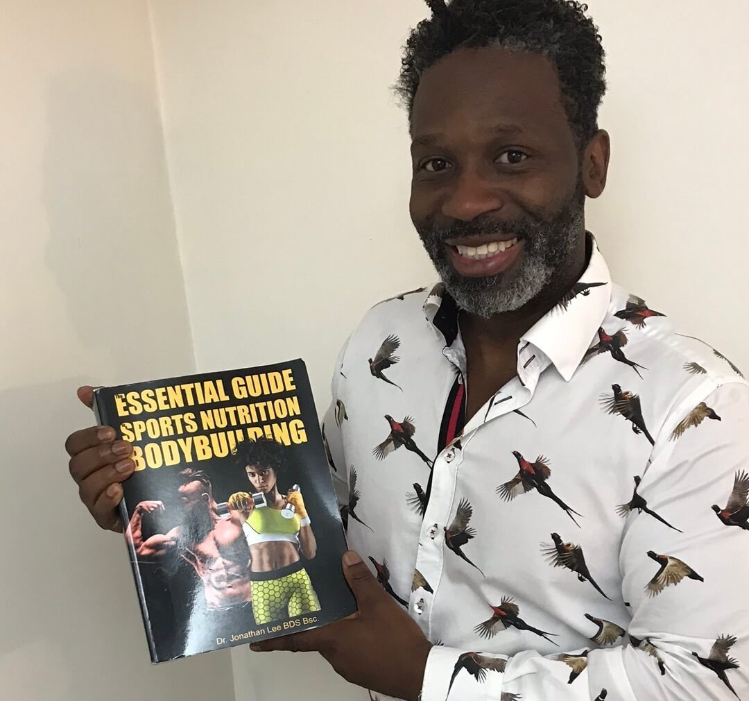 black man holding essential guide to sports nutrition and bodybuilding book